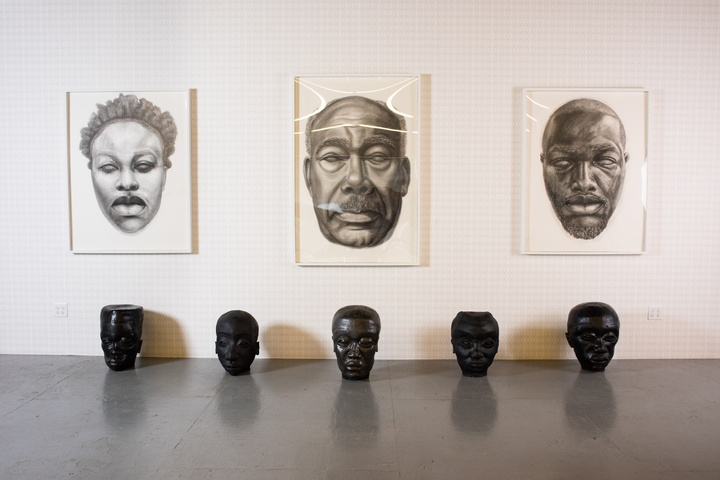 Three large-scale black and white drawings of heads with blank pupil-less eyes and a row of five black sculptural heads sitting on the floor below.