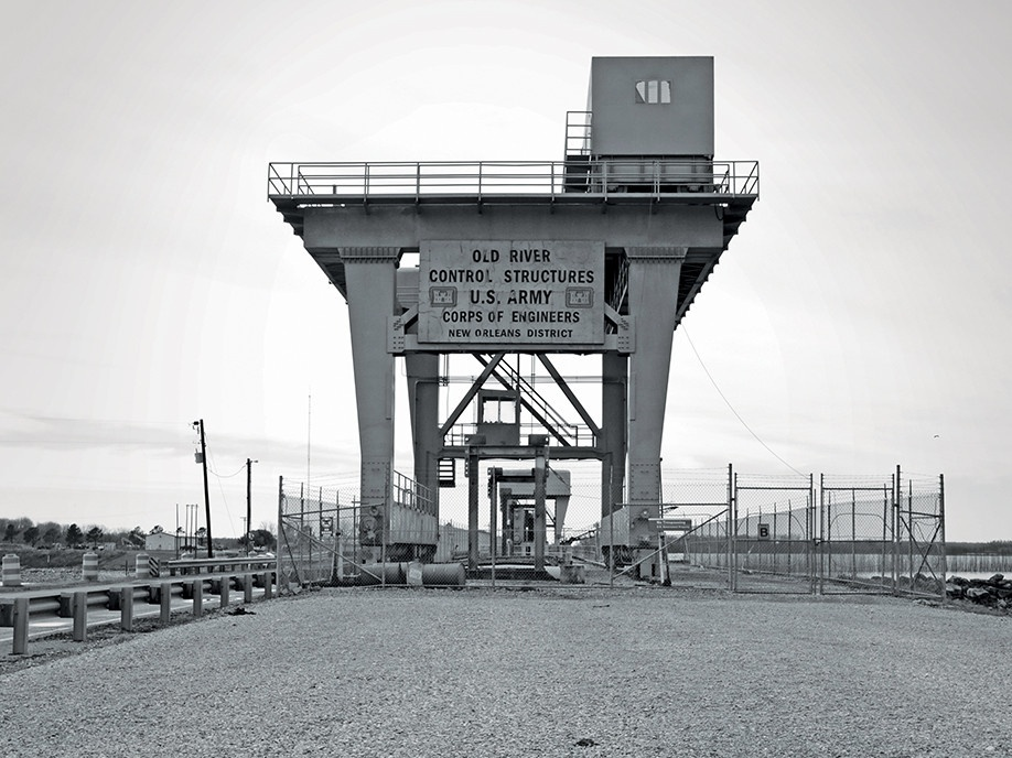 """Black-and-white photo of a river control structure in New Orleans. The sign says, """"Old River Control Structures U.S. Army Corps of Engineers New Orleans District."""""""