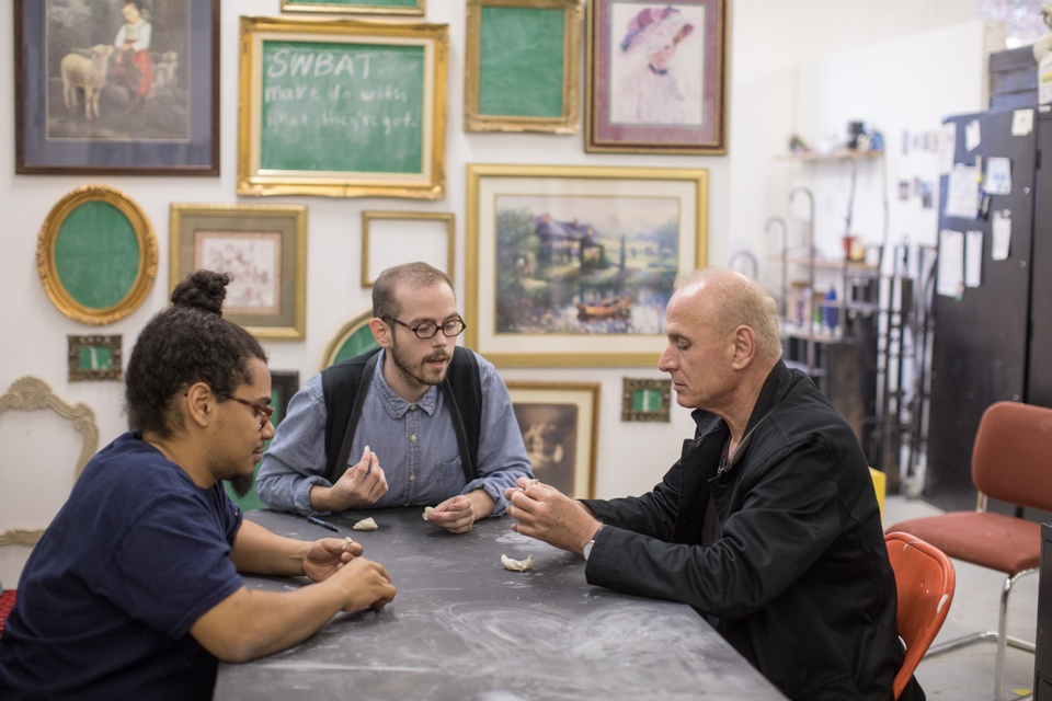 Three people sit at a table in a room hung with dozens of framed images. One person inspects a small white object while another leans toward them to explain something.