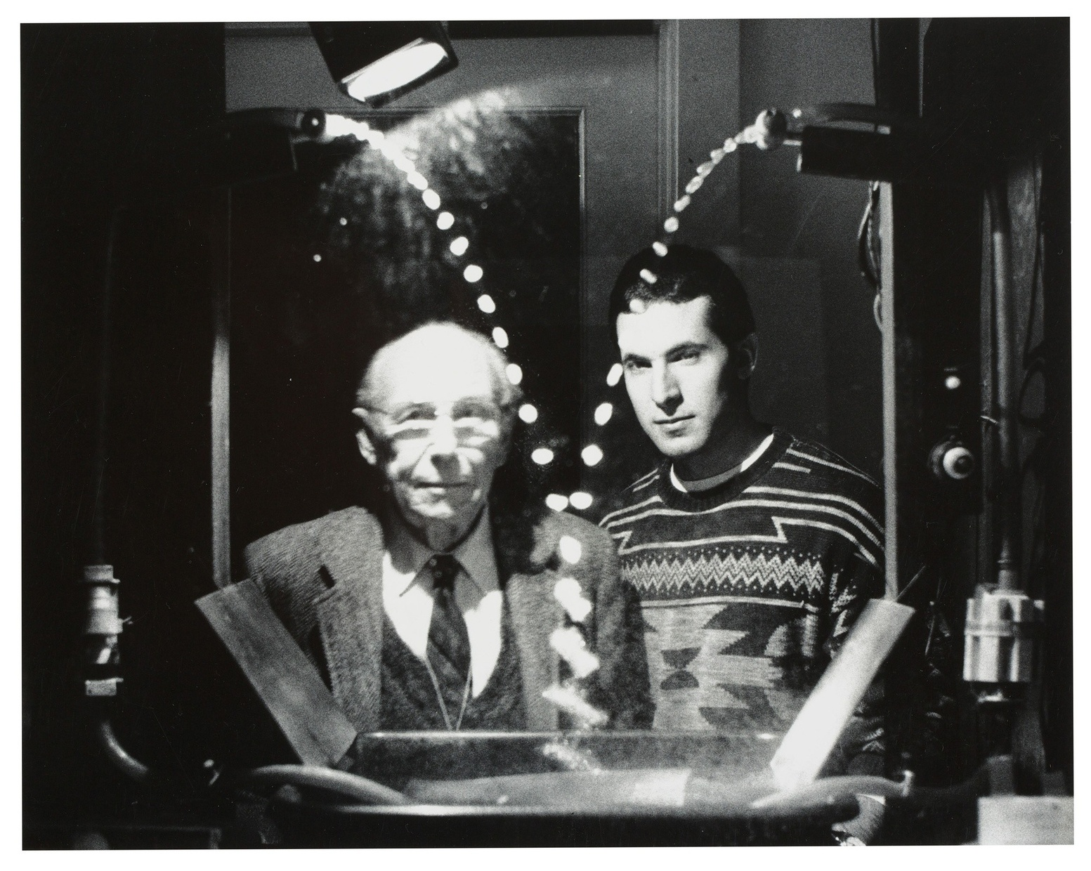 A black and white photograph of an old, light-skinned standing next to a younger, light-skinned man behind a contraption dripping water from two different sides.