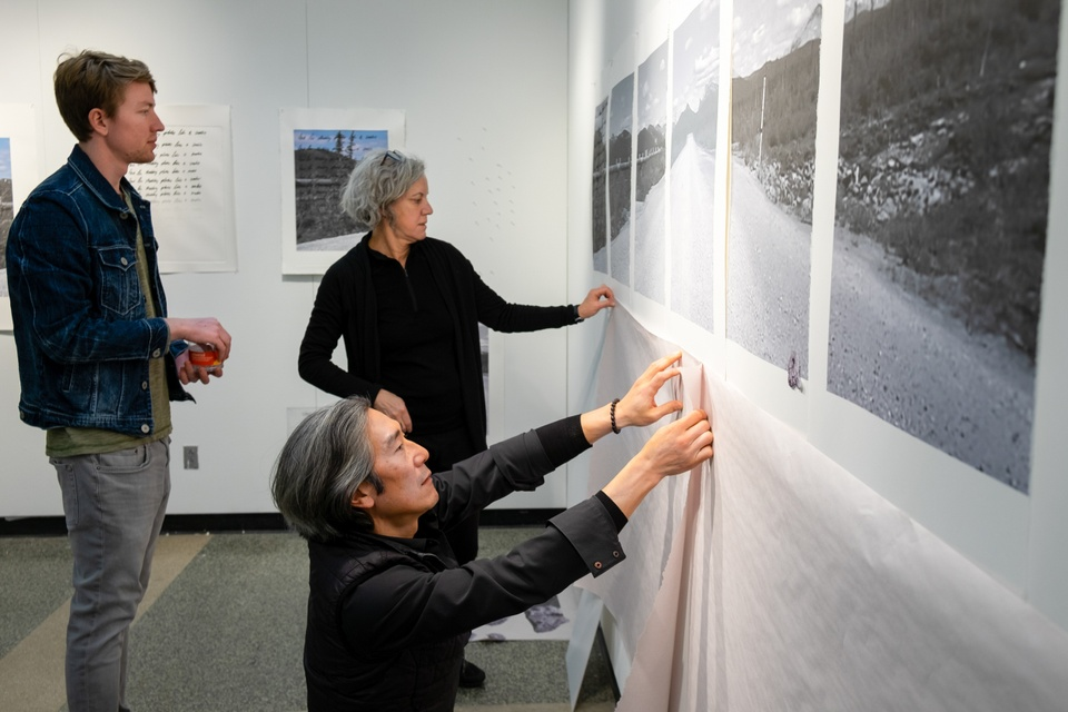 Three people pin up large printouts of black and white landscape photos in a white room.
