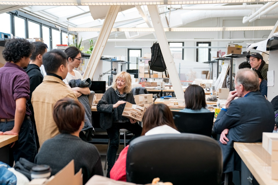 Top-floor studio space with full skylights and exposed I-beams and an open desk area that allows for a small gathering of people listening to an instructor.