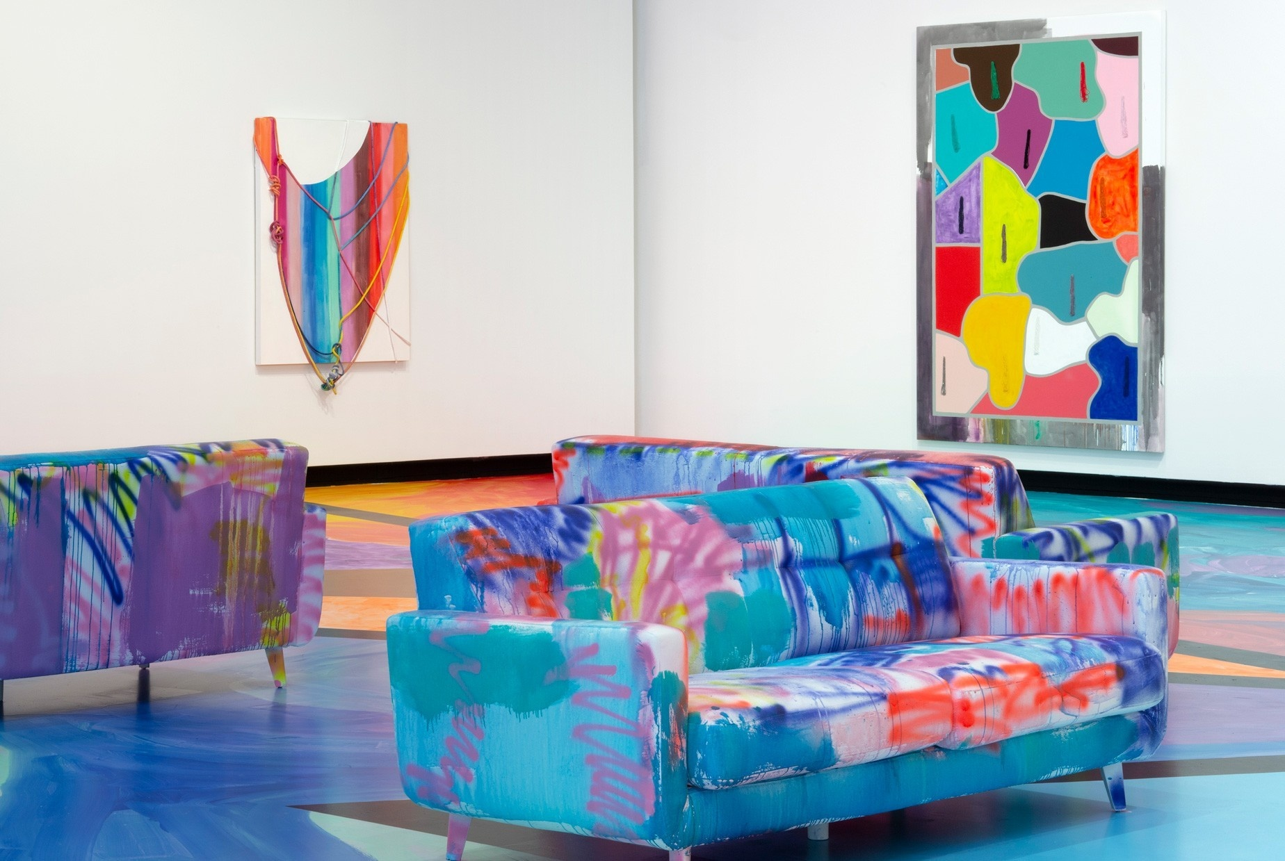 Three colorful painted couches, a colorful painted floor, and two colorful paintings on a gallery wall