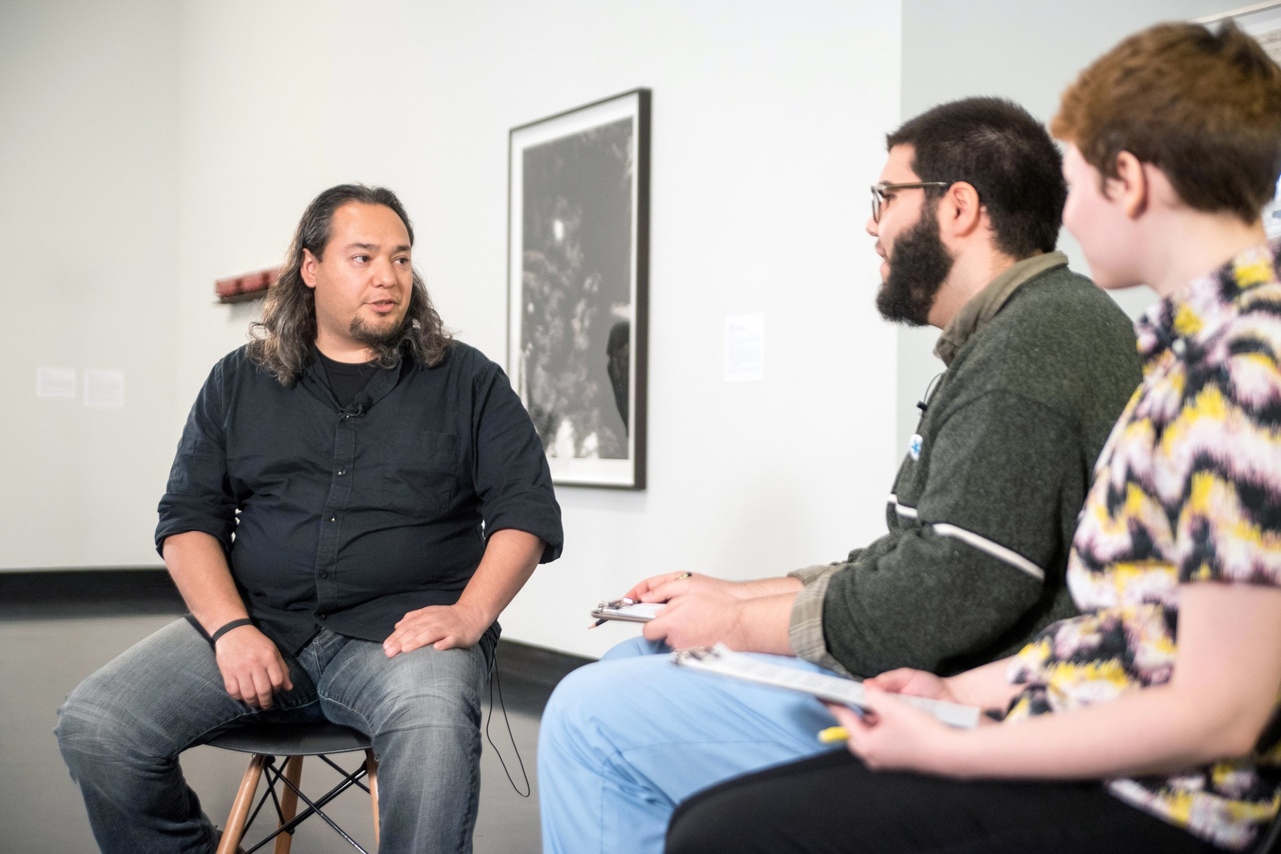 Artist Miguel Aragón, a tanned, Latino man, sits across from two Skidmore students during an interview in a gallery space.