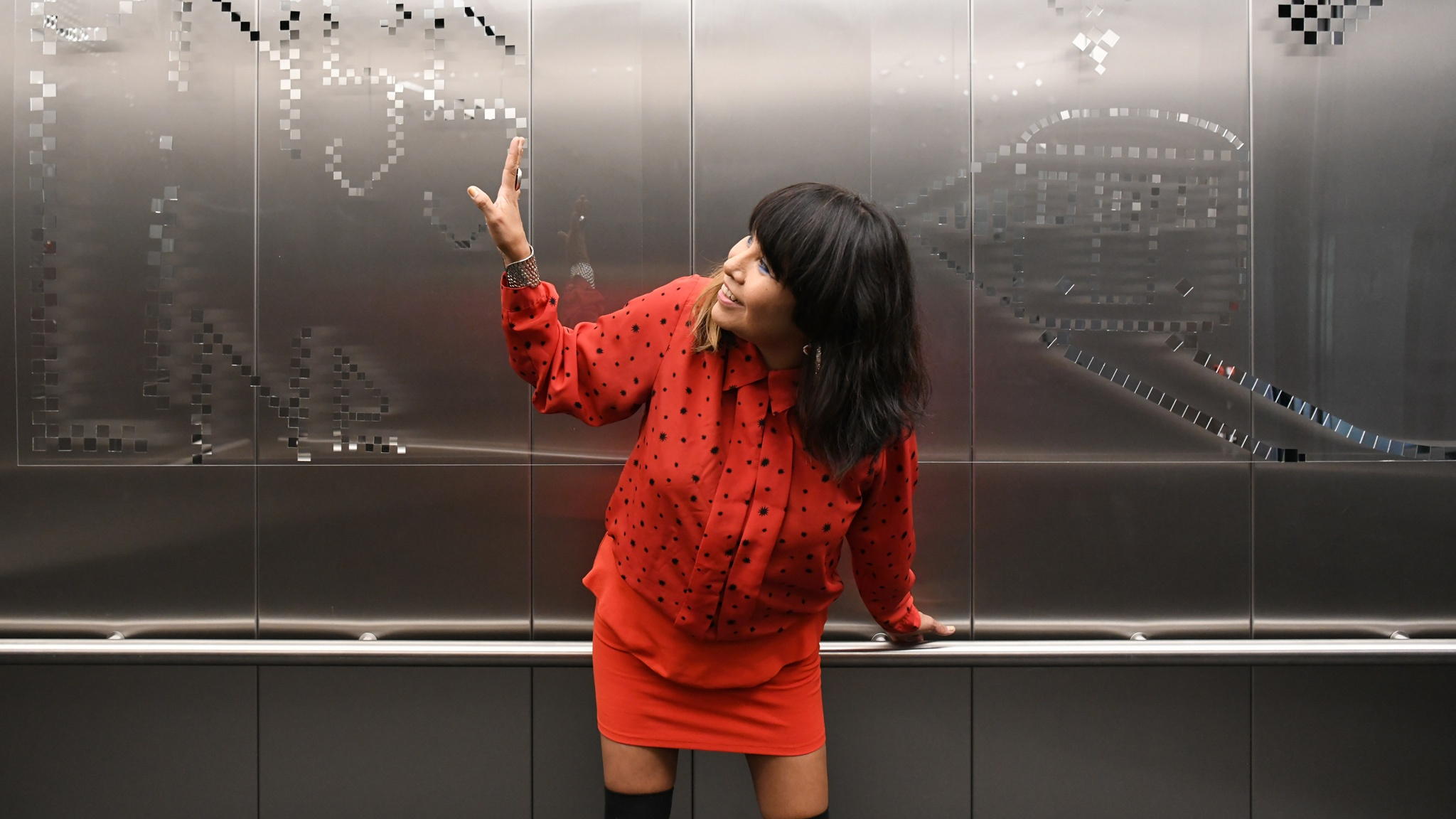 A woman wearing a red dress gestures to a pattern on the wall of an elevator behind her.