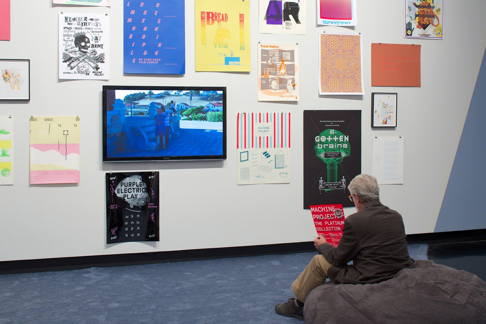 A man sits on a large bean bag chair holding a poster and facing a wall of posters.