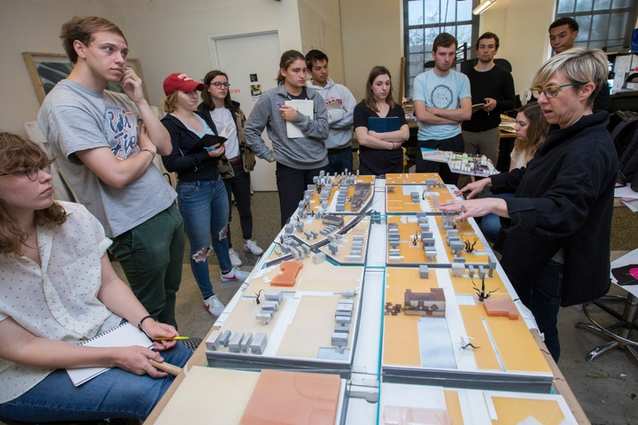 A class stands around a model of several city blocks and discusses.
