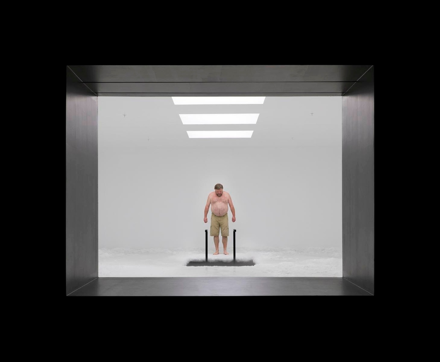 A black frame around a view into threshehold of a white room with three rectangular, overhead lights. A shirtless individual is looking down at a rectangular opening in the floor, with what might be a black ladder leading into it.