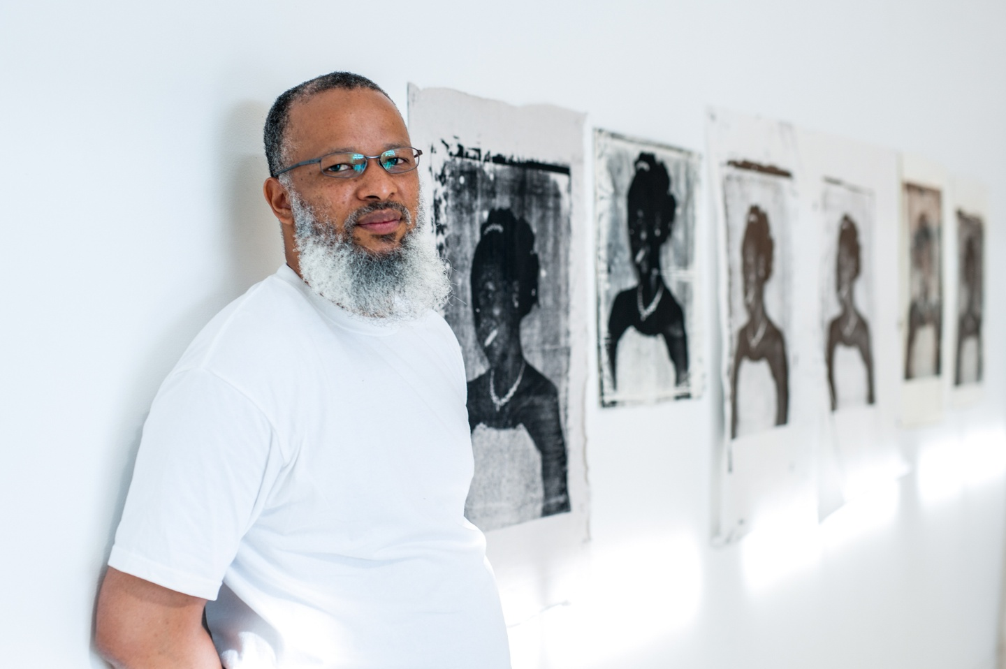 Portrait photo of Meleko Mokgosi in a gallery with framed, black-and-white artworks on white walls.