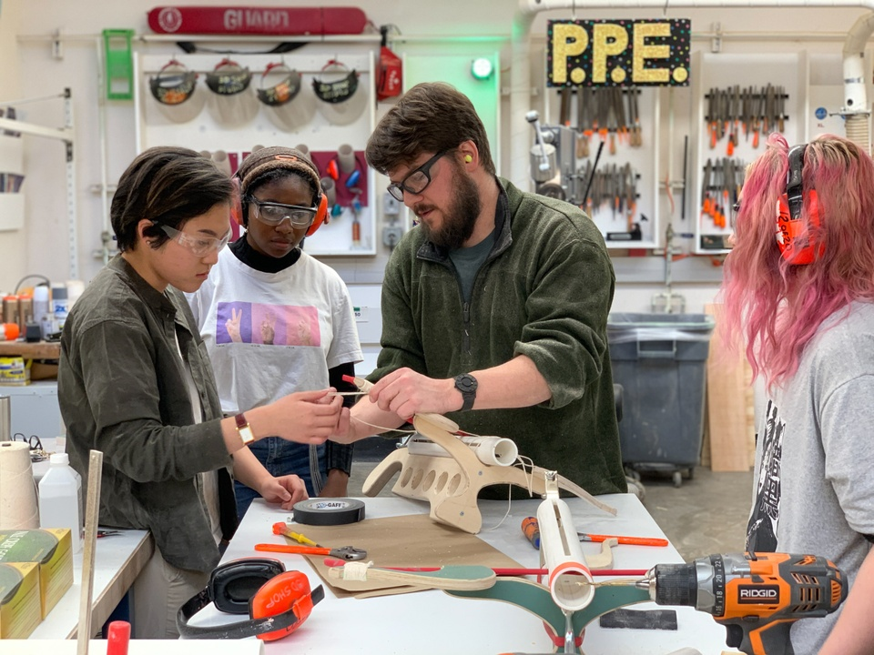 Instructor in a woodshop demonstrates stringing a ping-pong ball crossbow made of wood and PVC to a couple students.