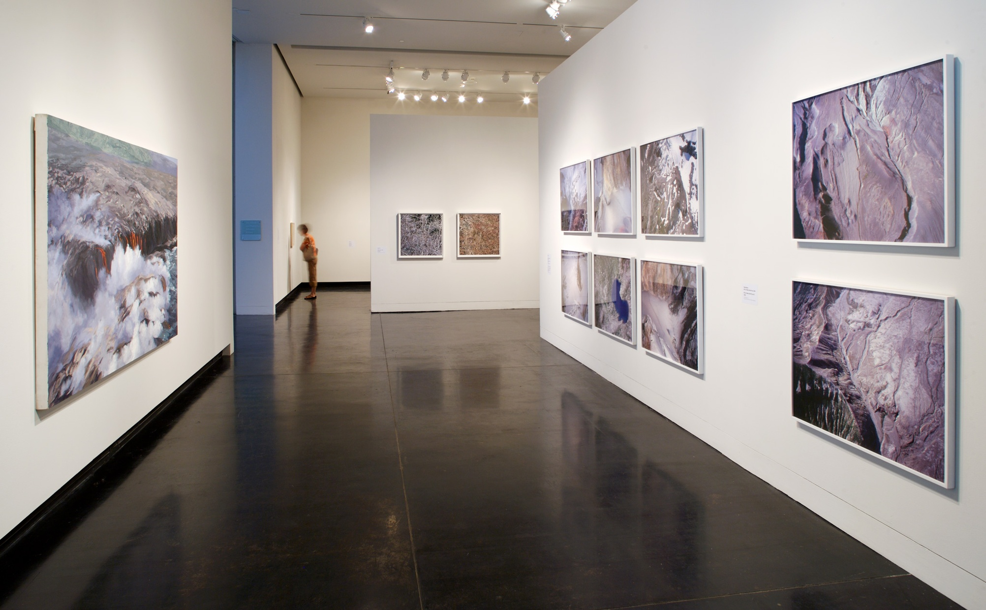 Framed photographs of geographic scenes hang on white walls in a gallery space.