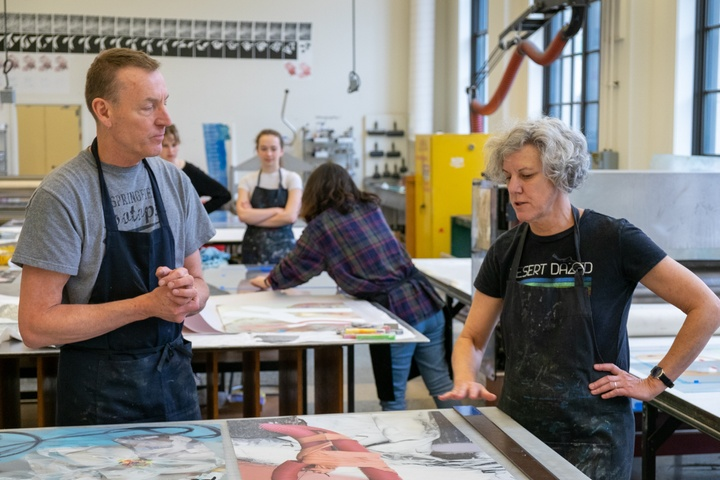 Two people discuss an image collage on a worktable in a printmaking studio while others prepare work behind them.