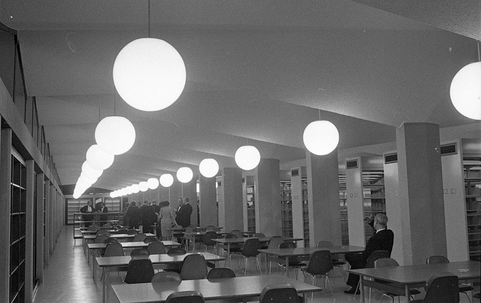 Black and white photo of a long room with a pleated ceiling and huge globe lights. There are rows of tables and chairs, and library stacks line the left wall.