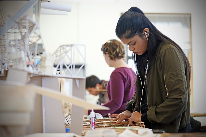 A student works at their desk in studio, with a white architectural model to her left; two other students work in the background.