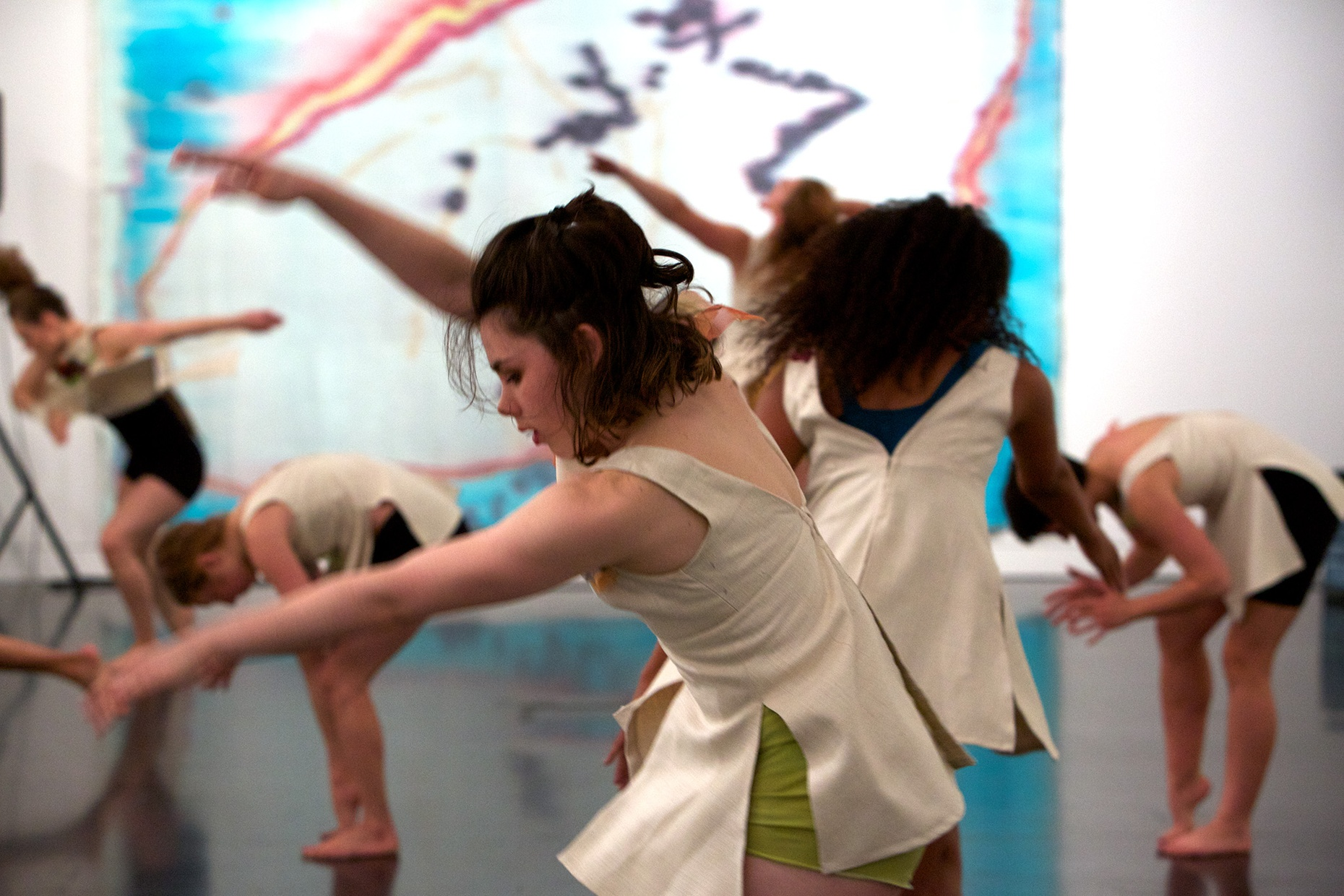 A white, female dancer caught in motion in front of a group of dancers in front of a large blue, red, white, yellow, and purple painting.