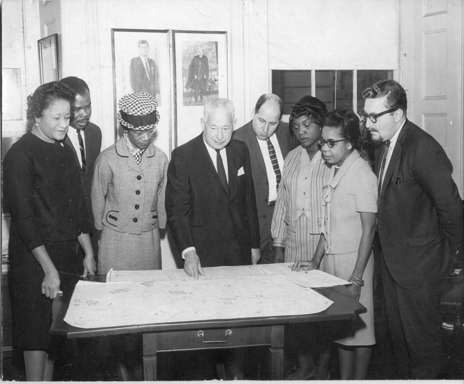 FIG. 1: In 1964 a group of ministers in Bedford-Stuyvesant requested tech- nical assistance from Pratt Center for Community Improvement (now Pratt Center for Community Development) to evaluate a city-sponsored urban renewal plan in their community. Pratt Institute's Ron Shiffman (far right) joins local leaders in presenting the Bedford-Stuyvesant Alternative Plan to then-Brooklyn borough president Abe Stark (center). Shirley Chisholm, then a New York state assemblywoman and later the first African American woman in the US Congress, stands to Stark's left (1966). Image is property of Pratt Center for Community Development.