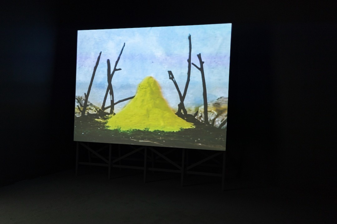 A towering projection screen with a wooden scaffold for a base appears in a dark theater. On the screen, a pyramid of bright yellow, sulphurous powder sits atop dark soil in the middle of a model landscape. Powder accumulates around the base of the heap, spreading out towards several blackened, spindly, upright twigs that resemble dead trees. Grey rocks appear on the outer edges of the makeshift horizon, pressed up against a mottled sky painted in blue and white.
