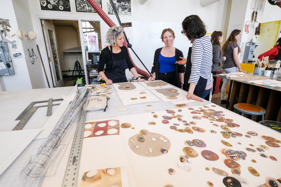 Three people stand around a worktable full of cut out images of eyeballs.