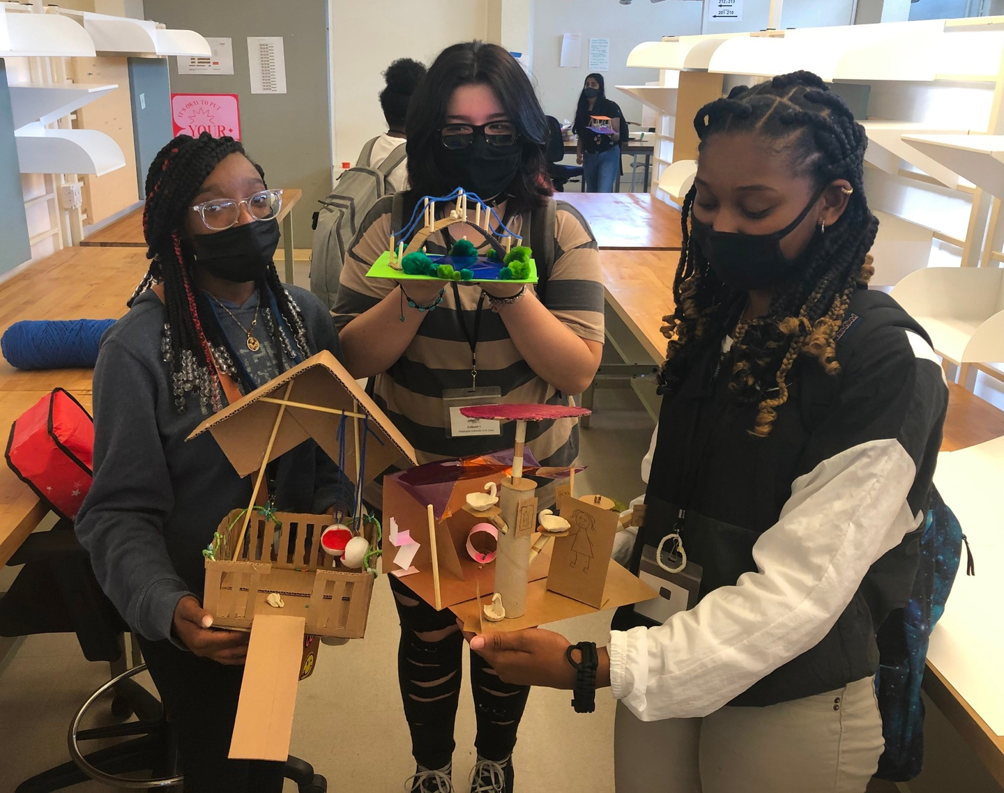 A group of three people wearing masks stands between desks, holding models made of wood and paper.