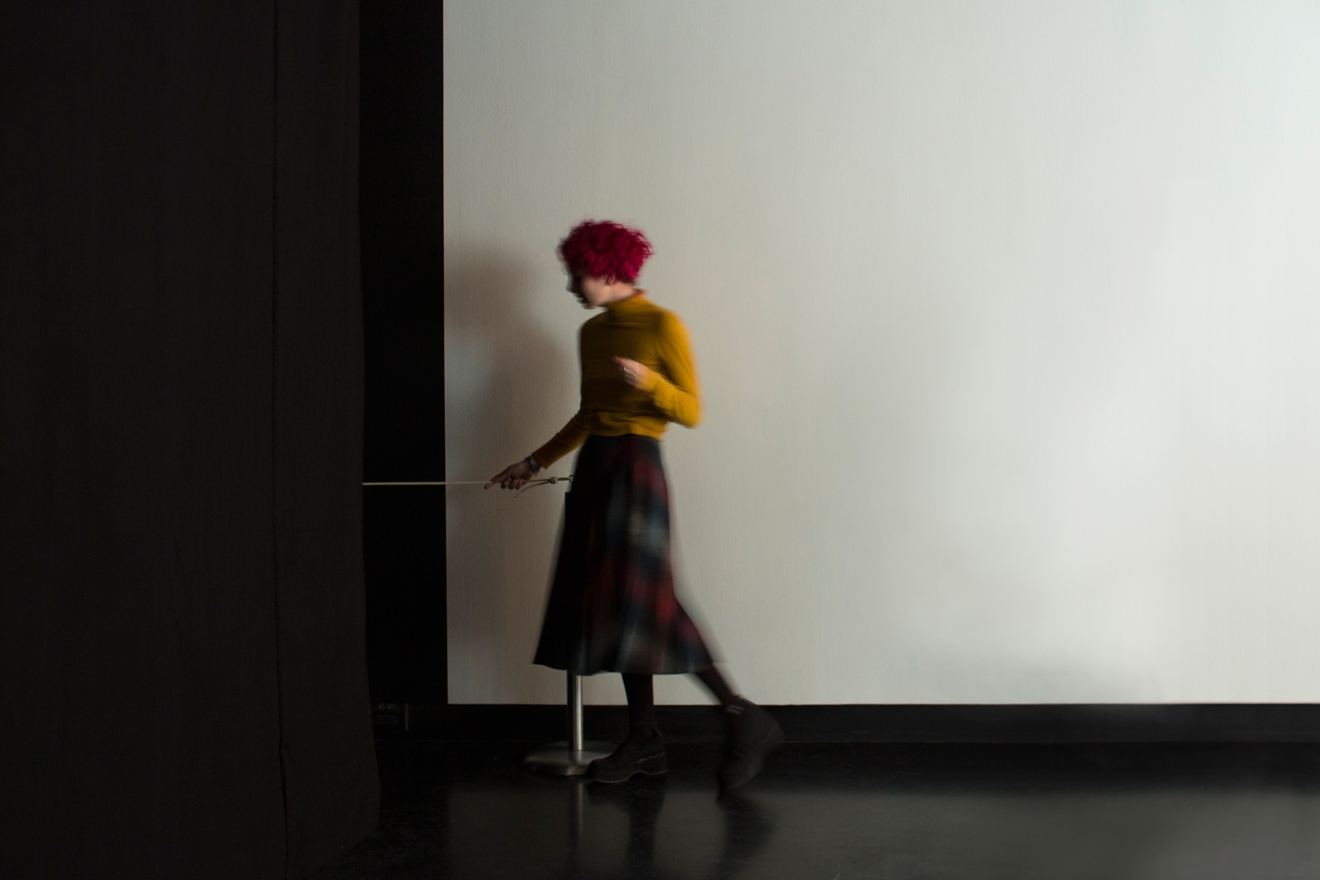 A light-skinned, young person walking into a dark room holding onto a rope attached to the wall.
