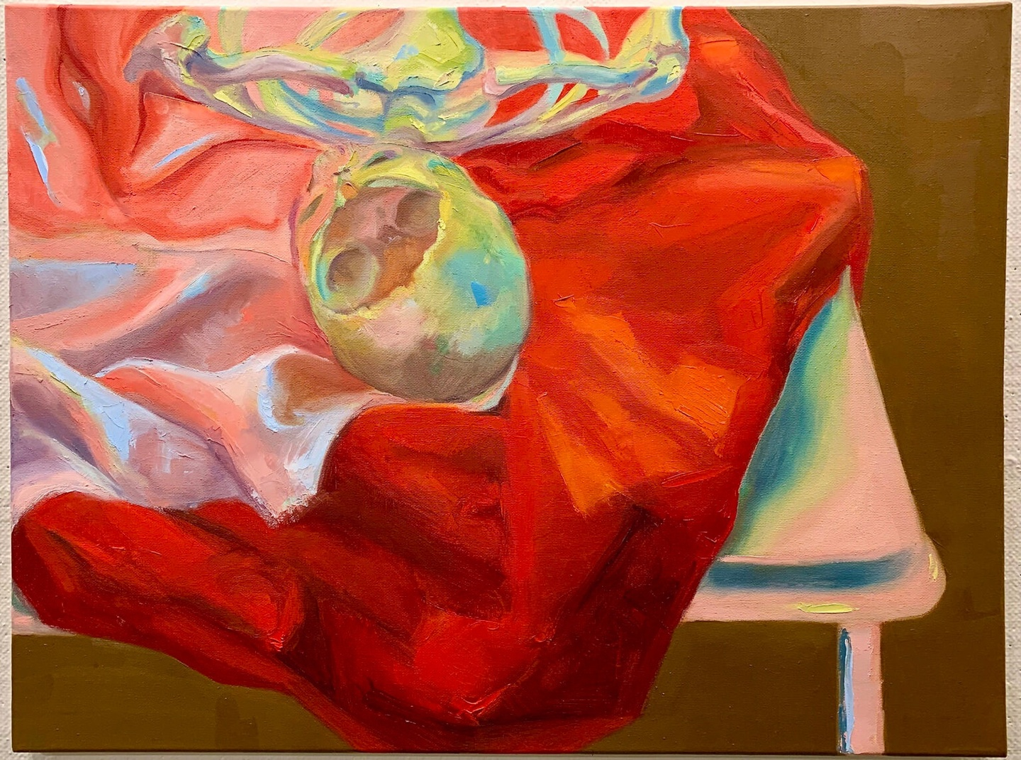 Oil on canvas painting of a skull atop a red/pink draped fabric on a table.