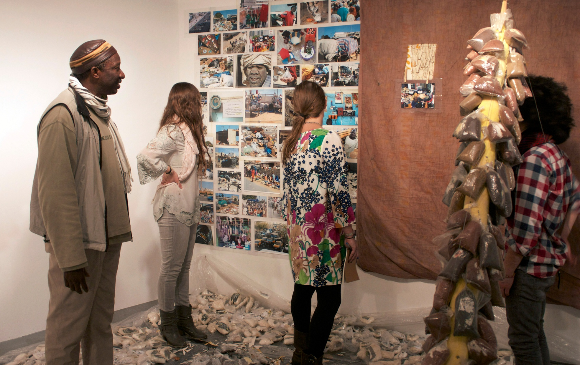 Four people stand on a plastic- and rubbish-lined floor looking at a variety of photographs next to a sculpture made with wood and bags of dirt.