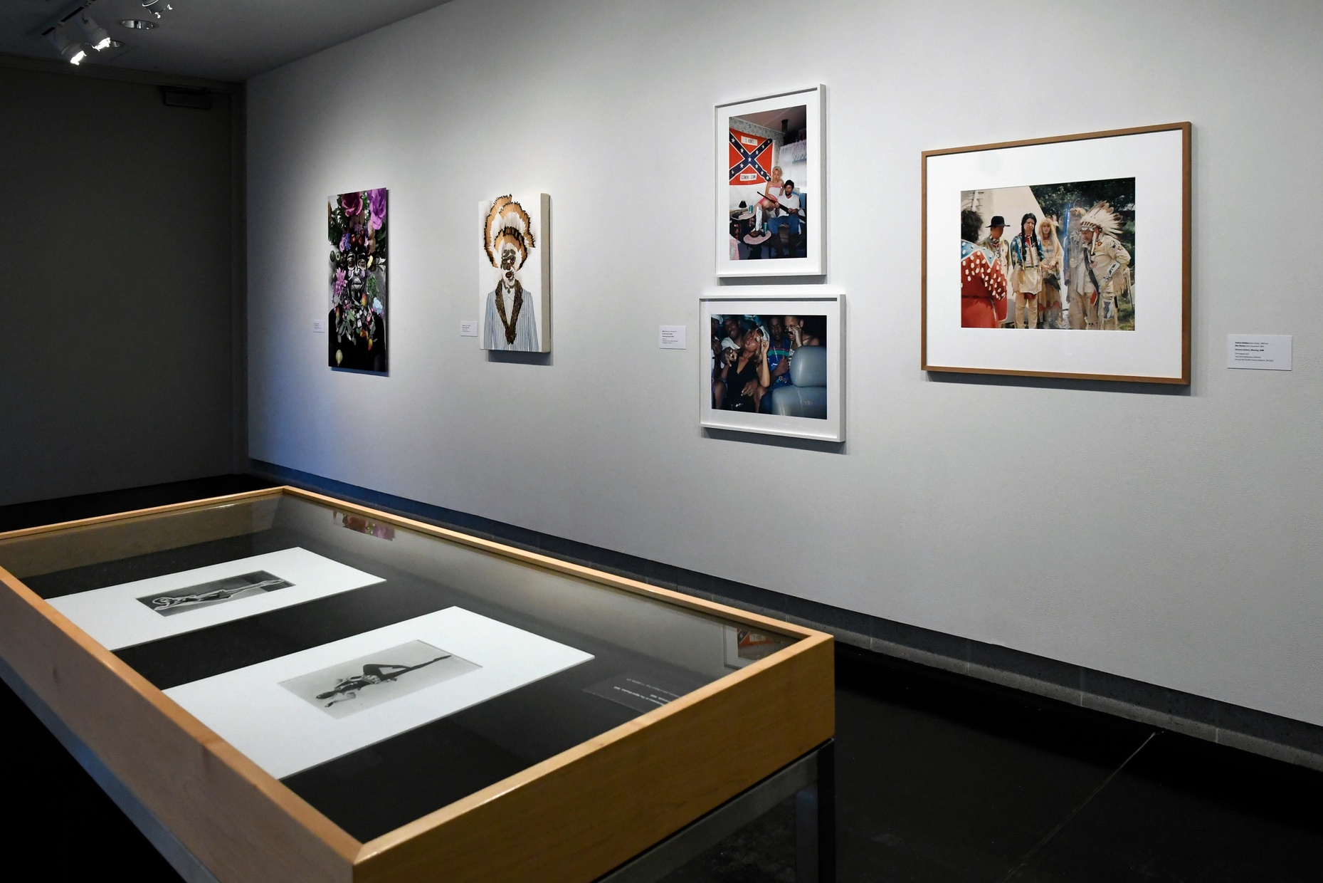 Five photographs of people hang on a gray wall with a case holding two black and white photographs visible in the foreground.