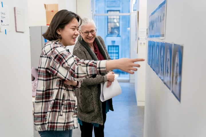 Two people look at some prints pinned to the outside wall of an artist's studio.