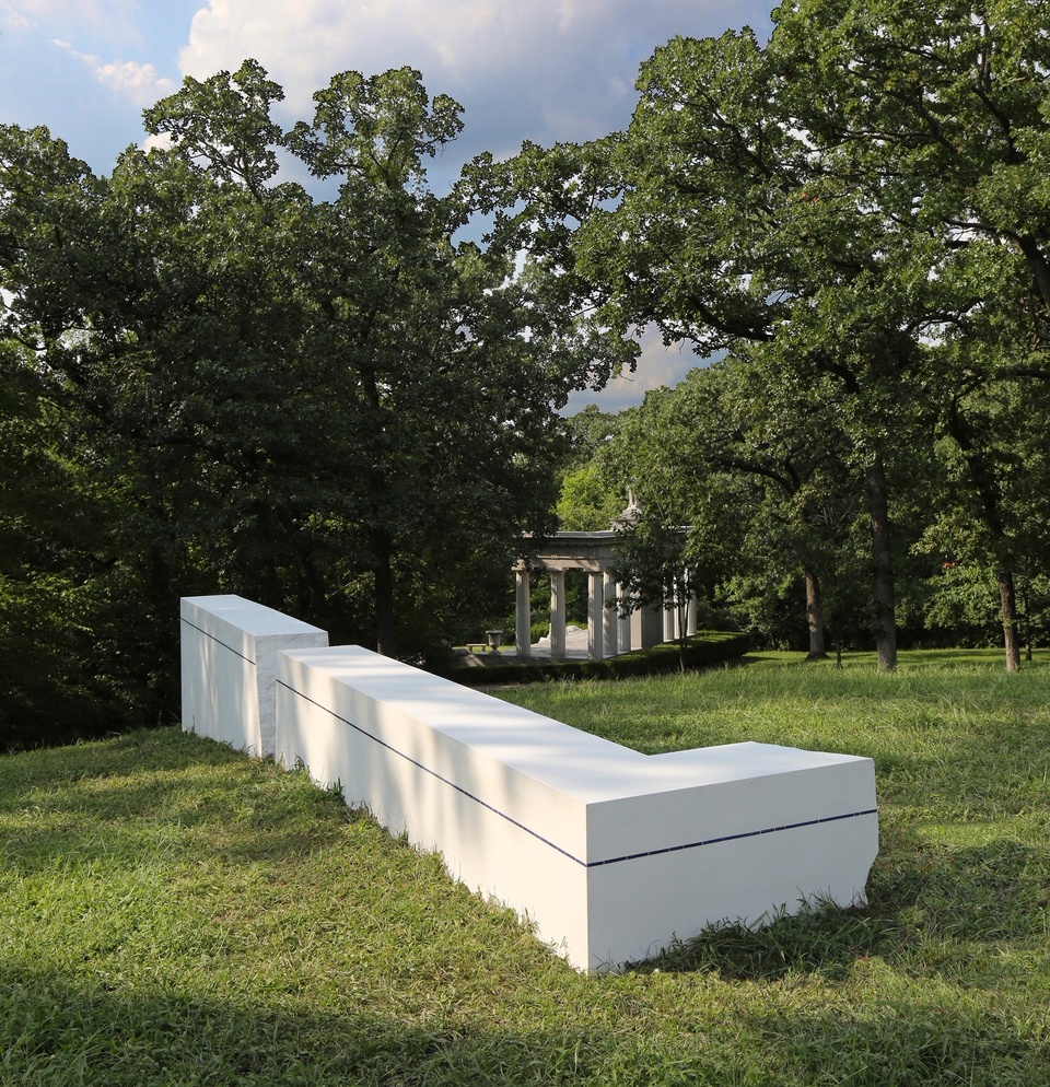 An 'L' shaped white concrete sculpture with a dark blue line on its sides on a grassy plain