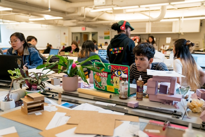 Large group of students work on models and laptops surrounded by model-making supplies in an open format work area.