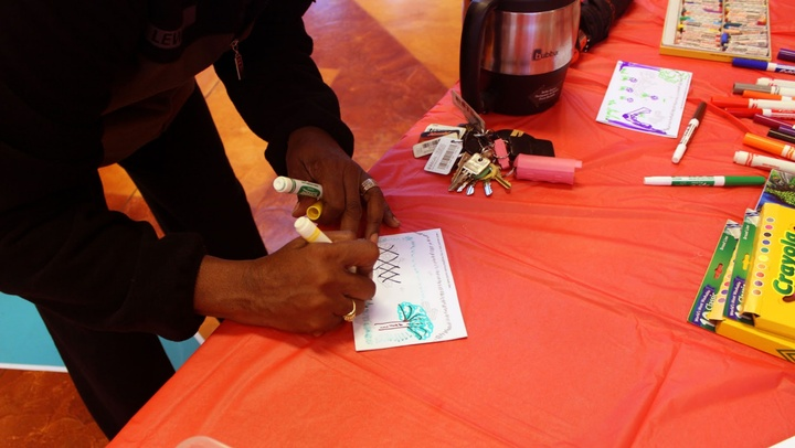 A person holding a marker writes on a postcard on a table with other markers and postcard supplies.