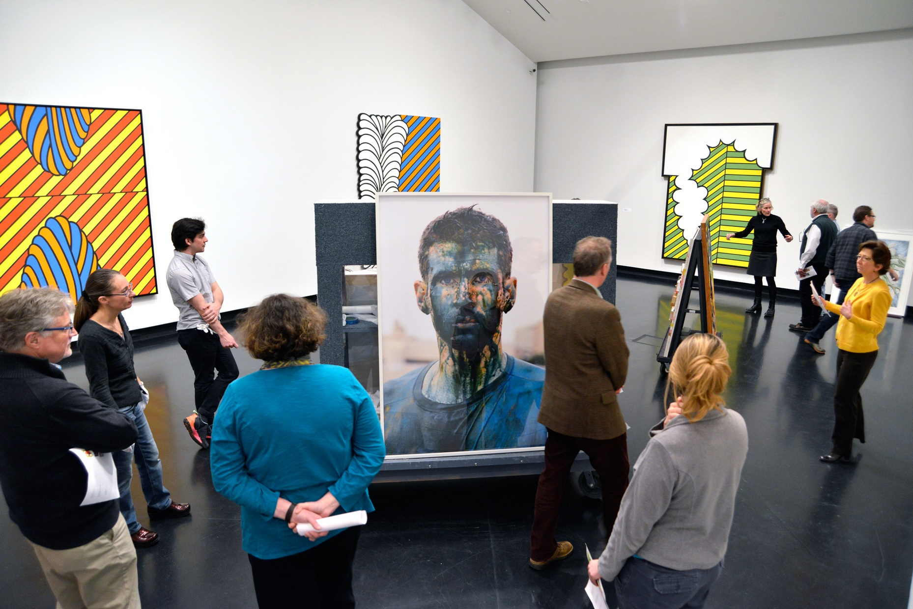 A group of people scattered throughout a gallery space with large, colorful, abstract prints on the walls and a large photograph of a young, white man with blue paint on his face sitting in the center of the gallery.