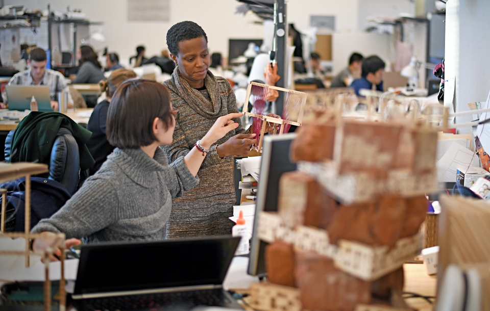 Deep studio space with dozens of students and semi-private desks piled high with models.