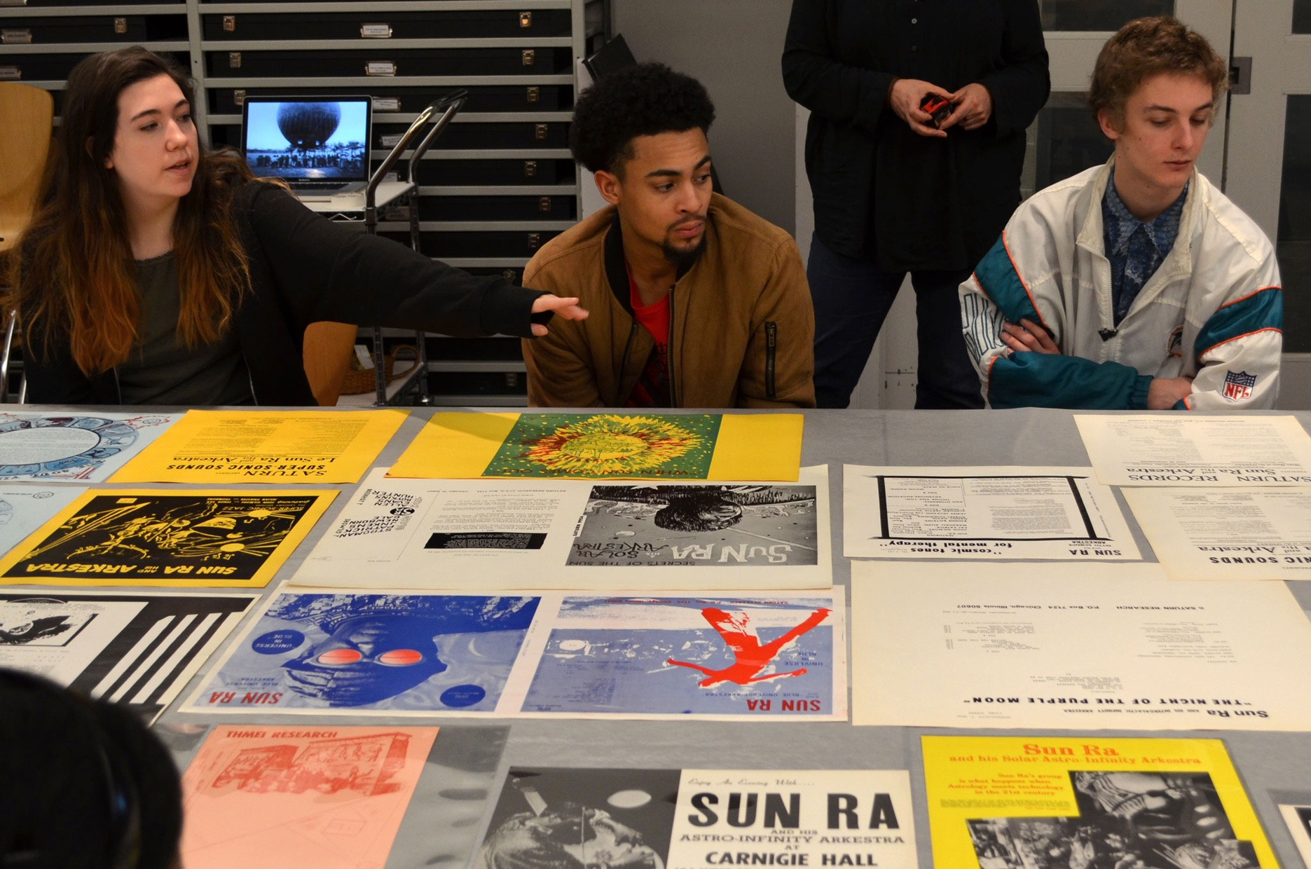 Three students sit behind a table covered in colorful prints and album covers.