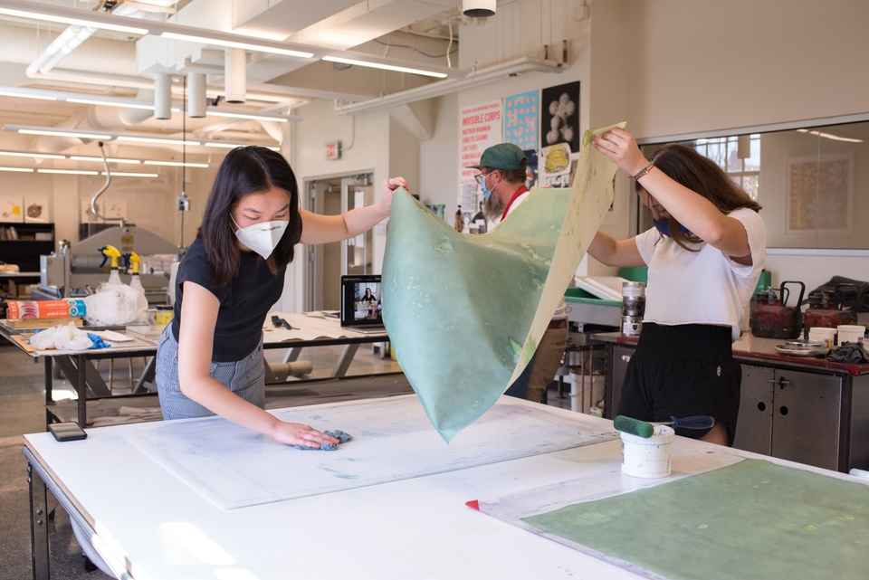 Two people lift up a cyanotype print and scrub the plexi plate beneath it.