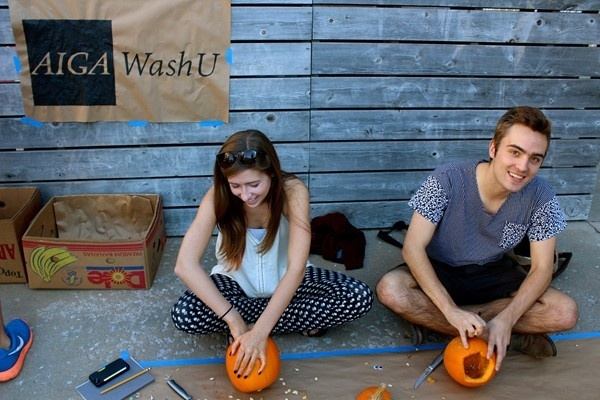 Two students carving pumpkins in front of a wall. The AIGA WashU logo on brown paper hangs from the wall.