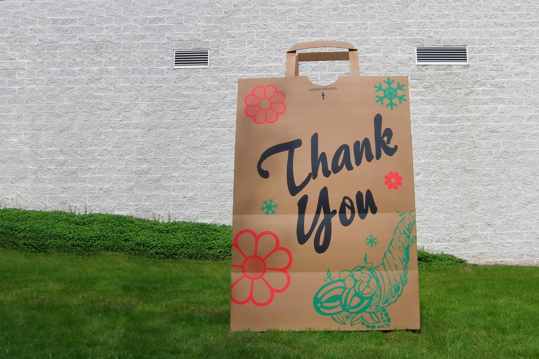 """A large sculpture of a brown paper bag with """"Thank you"""" written on it in black script in front of a gray brick building."""