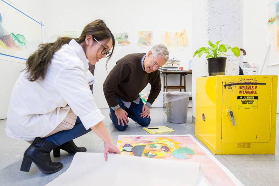 Two people crouch over a large sheet of paper with collaged pieces on the floor of an artist's studio.