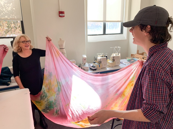 Two people stretch a piece of finished pink shibori dyed fabric out.