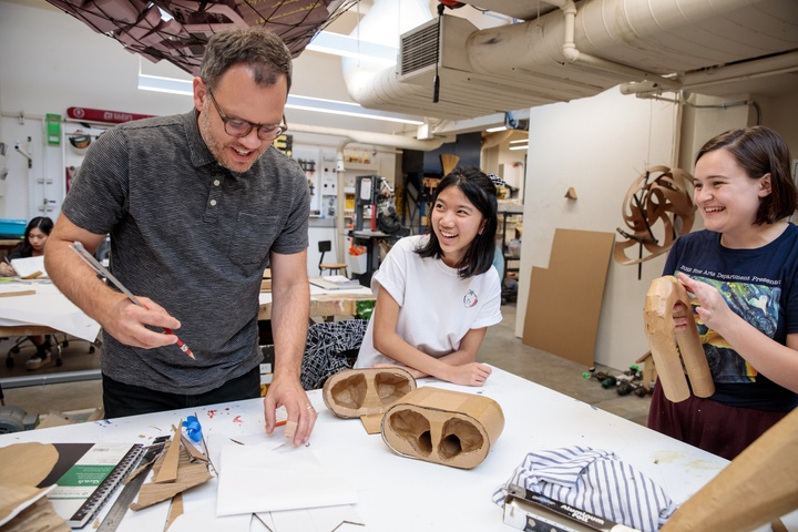 Three people stand around a worktable looking at a giant cardboard model of a AirPods case and associated plan drawings, laughing.