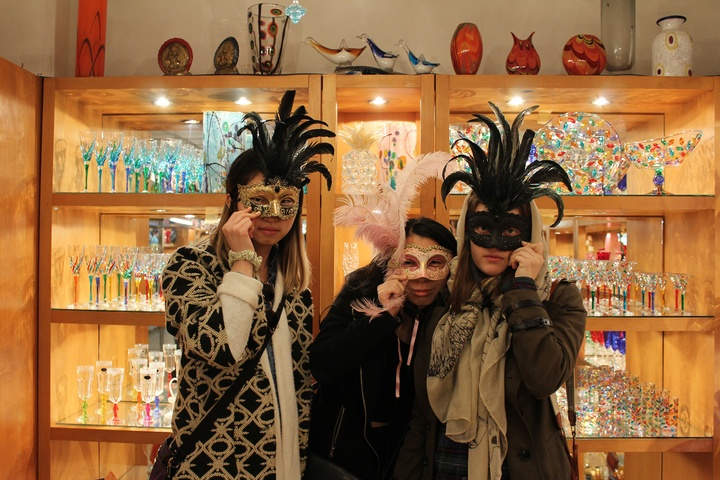 Three people in a glass shop holding ornate carnival masks over their eyes