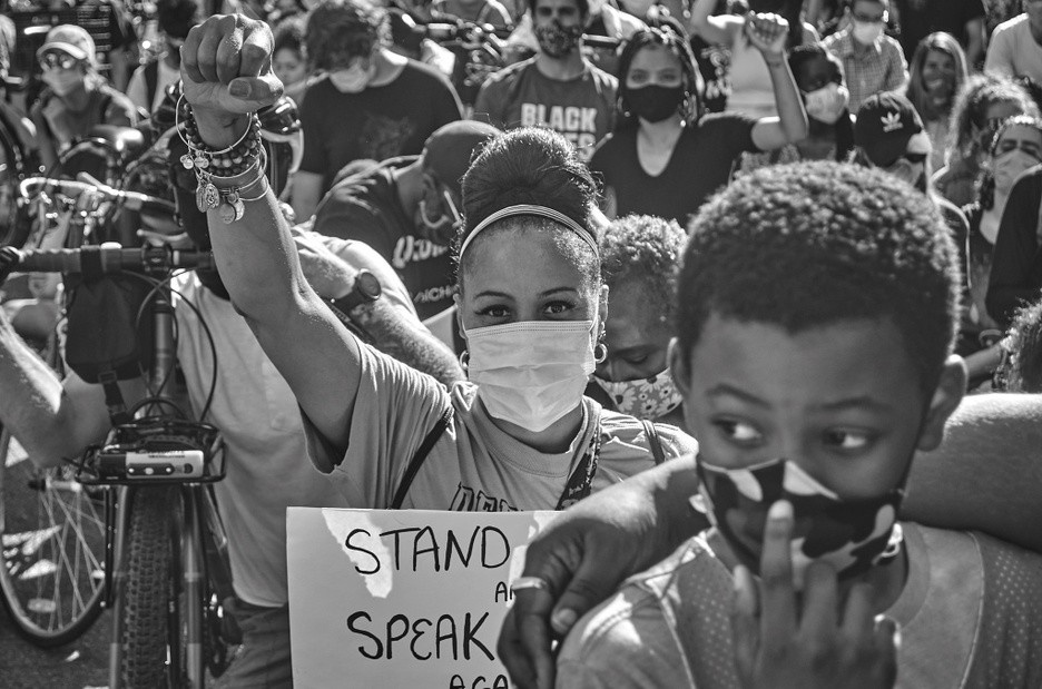 A black and white photograph of a crowd of protestors centered around a young, dark-skinned female wearing a mask, holding a sign and raising her right fist in the air.