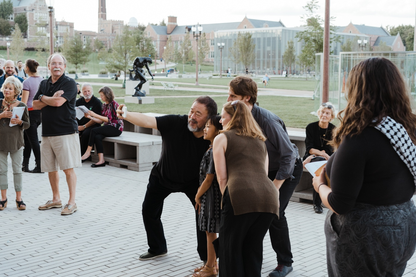 Artist Ai Weiwei takes a selfie with a few attendees at his exhibition opening. Everyone is gathered outside, in front of the green park area outside the Kemper Art Museum; other onlookers and patrons mingle.