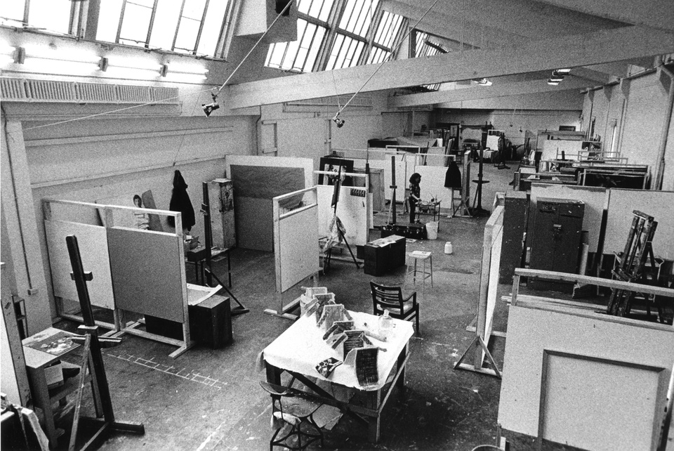 Black and white photo of an overhead view of a large studio space filled with artists' cubicles. An angled skylight along one side of the room fills the room with natural light.