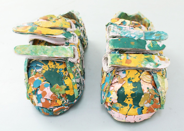 Pair of velcro closure shoes covered in layers of paint blotches in yellow, teal, and shades of pink and clay.