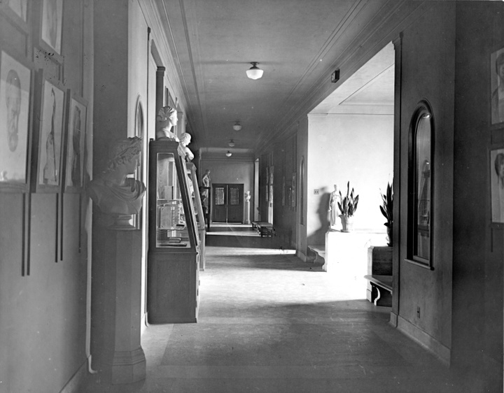 Black and white photo of a hallway filled with sunlight, displaying various paintings and classical sculptures.