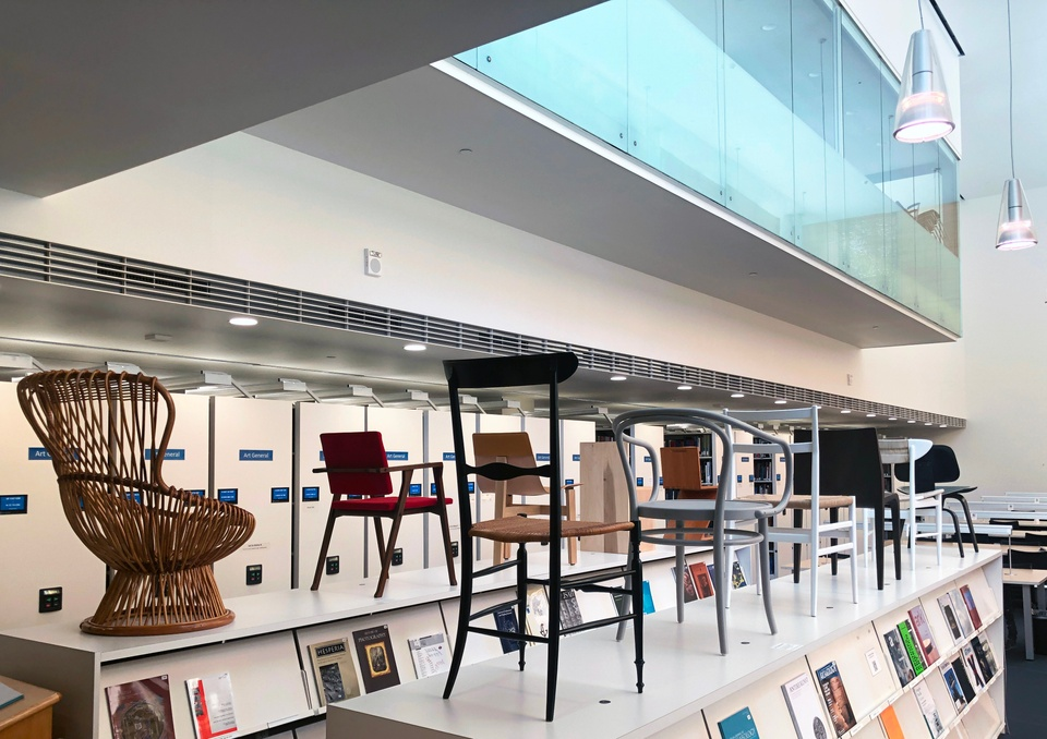 Exhibition of several architectural chairs, displayed atop a pair of magazine shelving units in the library.