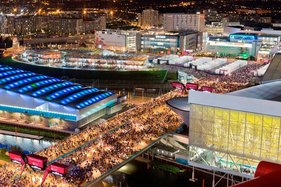 Nightime aerial photo of the scene at the London Olympic and Paralympic Games. The scene includes a venue with bight blue rooftop lights to the left, and a multilevel rectangular stucture with tall, yellow windows on the second floor. Between the two buildings is an open spaces dotted with large crowds of people. In the background is a view of more buildings lit up.