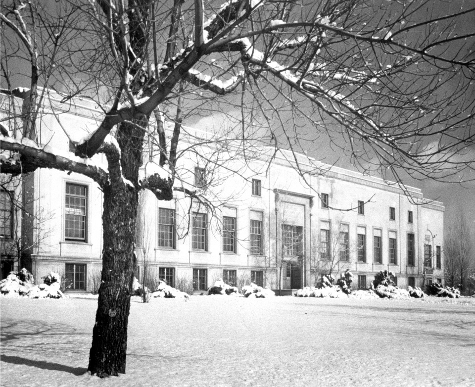Black and white photo of a Beau-arts era building in the snow.