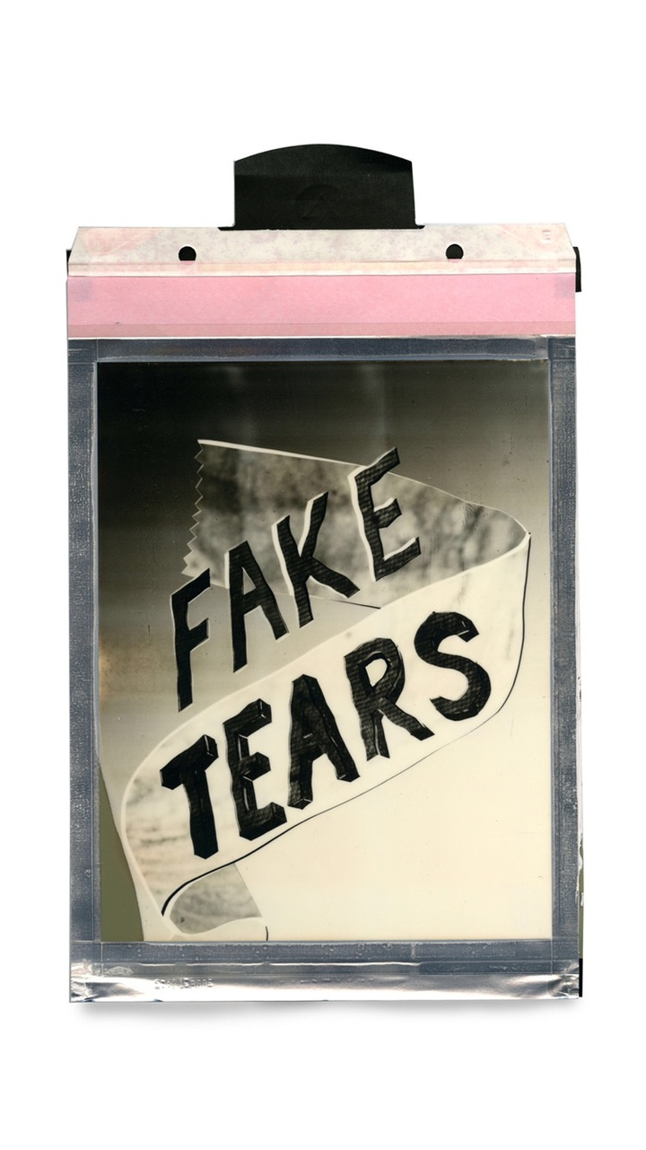 A polaroid of the text 'Fake Tears' with a ribbon over it